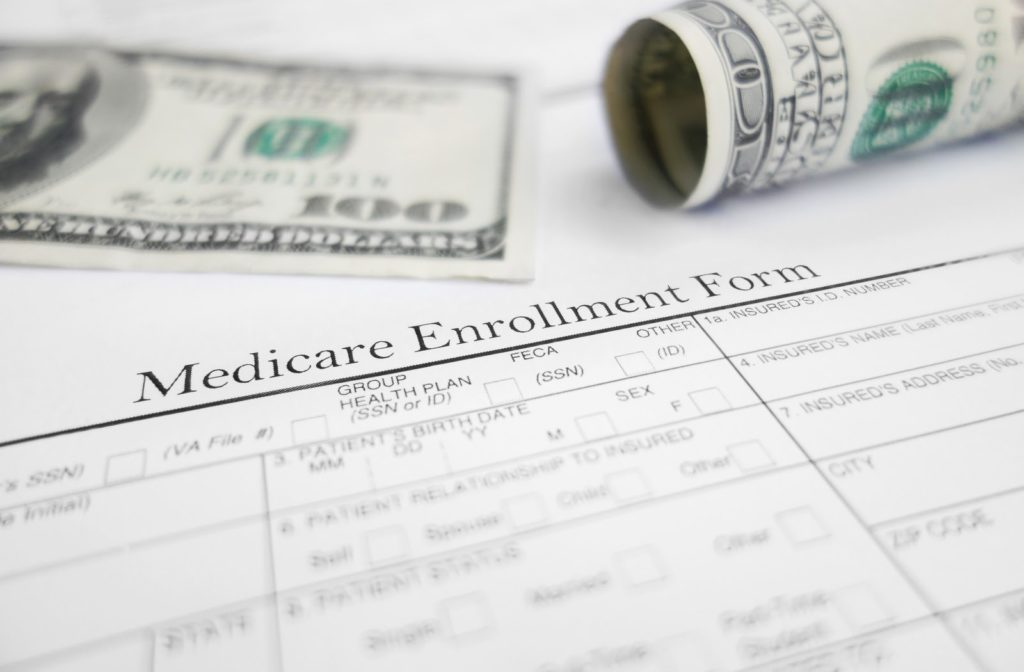 Medicare enrolment form with money bills in the background