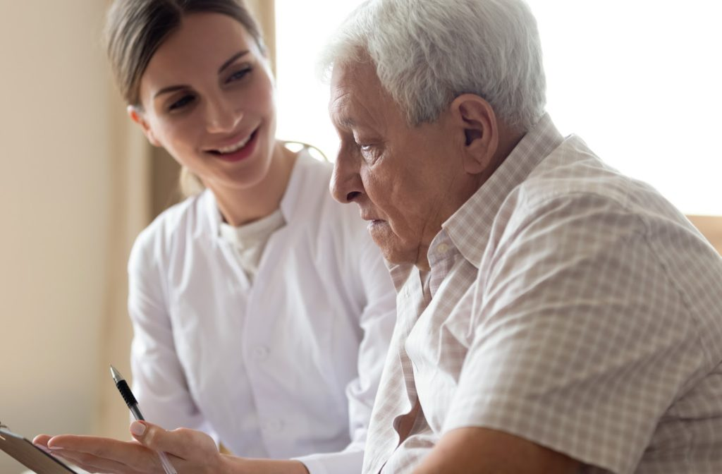 Senior man talking to nurse regarding  payments available for assisted living